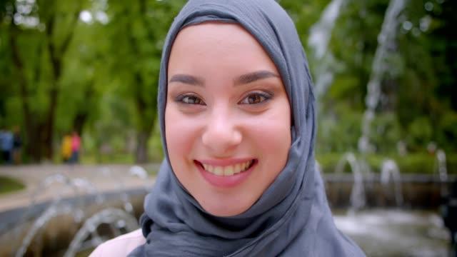 close-up portrait of pretty muslim student in hijab smiling sincerely and gladly standing near the fountain. - abbigliamento religioso video stock e b–roll
