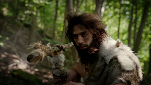 close-up portrait of primeval caveman wearing animal skin and fur hunting with a stone tipped spear in the prehistoric forest. prehistoric neanderthal hunter ready to throw spear in the jungle - cacciatore video stock e b–roll