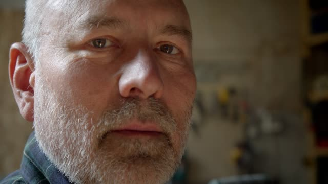 Close-up portrait of senior carpenter at wood manufacture watching into camera being serious and calm.