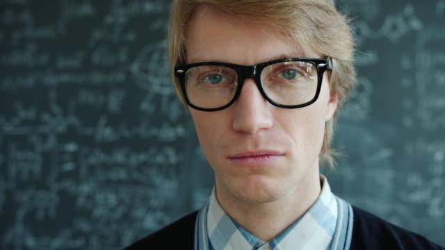nahaufnahme porträt von ernsthaften intelligenten mann trägt brille blick auf die kamera in innenräumen - vorlesungsfrei stock-videos und b-roll-filmmaterial