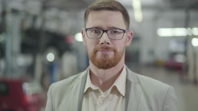 närbild porträtt av smart kaukasiska man med rött skägg tittar på kamera och gest ja genom att skaka huvudet. vuxna manliga bilhandlare poserar i bakgrunden av utställningslokalen. bilhandlare, bilaffärer. - rött hår bildbanksvideor och videomaterial från bakom kulisserna