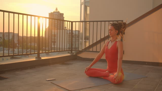 closeup portrait of spiritual female with dreadlocks practicing yoga lotus on rooftop with beautiful city landscape sunset on background - balcone video stock e b–roll