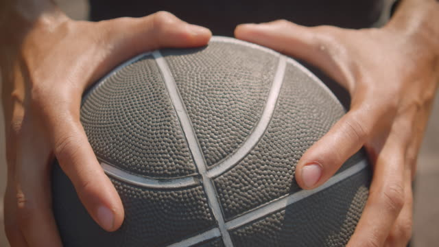 Closeup portrait of sporty african american male hands holding a basketball ball on the court in the urban city outdoors with bridge on the background