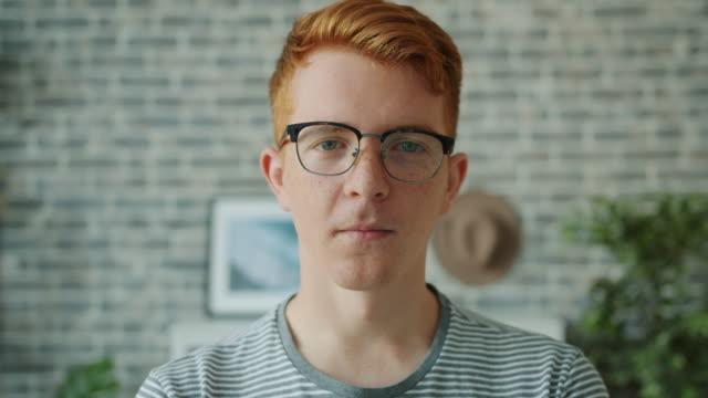 vídeos y material grabado en eventos de stock de retrato de cerca del adolescente mirando la cámara con la cara seria y luego sonriendo - sonrisa con dientes