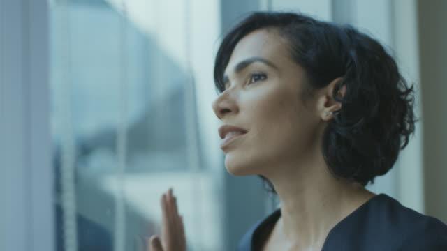 närbild porträtt av den vackra ung affärskvinna tittar fundersamt ut hennes office fönstret. trygga och attraktiva spansktalande kvinna tänker på hennes affärsprojekt. - titta på utsikt bildbanksvideor och videomaterial från bakom kulisserna