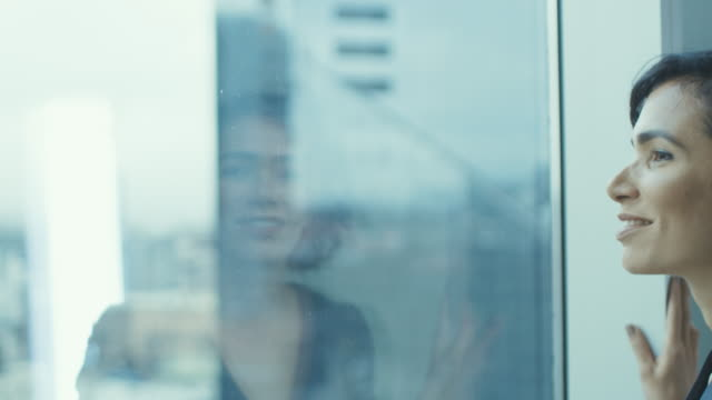 närbild porträtt av den vackra ung affärskvinna tittar fundersamt ut hennes office fönster med utsikt över stadsbilden. trygga och attraktiva spansktalande kvinna tänker på hennes affärsprojekt. - titta genom fönster bildbanksvideor och videomaterial från bakom kulisserna
