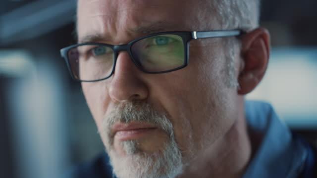 Portrait rapproché du bel homme âgé moyen portant des lunettes travaillant sur l'ordinateur. Homme aux cheveux gris attrayant avec les yeux bleus - Vidéo