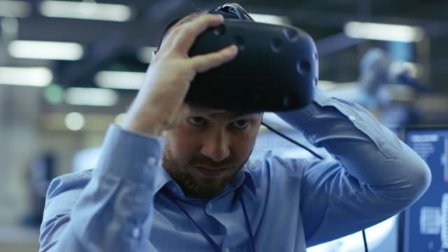 yakın çekim portre sanal gerçeklik kulaklık, çalışmaya hazır endüstri mühendisi koyarak. arka planda üretim tesisi ve monitörler. - sanal gerçeklik stok videoları ve detay görüntü çekimi