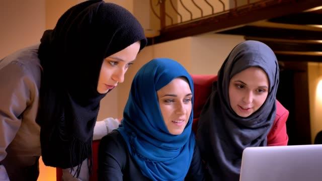 närbild porträtt av tre vackra arabiska affärs kvinnor som arbetar tillsammans och använder den bärbara datorn sedan titta på kameran leende - islam bildbanksvideor och videomaterial från bakom kulisserna