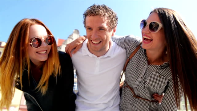 Closeup Portrait of Three Young People at the Old City Square in Sunny Warm Day. Smiling Faces of Happy Friends Enjoying Summer and Sunlight Outdoors video