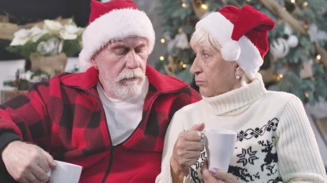 Close-up portrait of upset mature Caucasian man and woman sitting with coffee at the background of decorated Christmas tree. Old couple waiting for children on New Year's eve. Cinema 4k ProRes HQ.