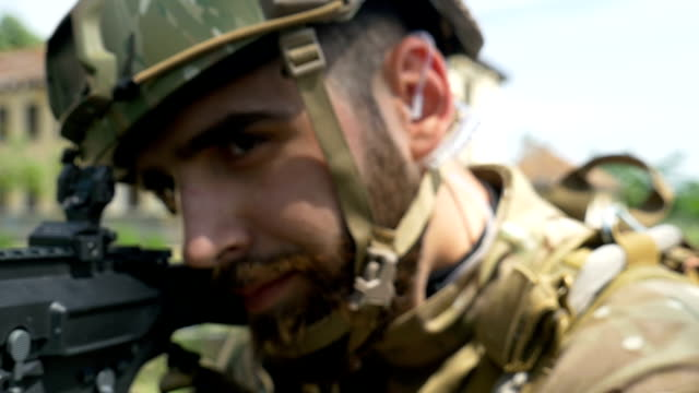 Closeup portrait of young army ranger aiming gun during a military training video