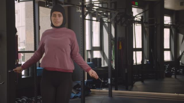 närbild porträtt av unga attraktiva atletisk muslimska kvinnliga hopprep i gymmet inomhus - anständig klädsel bildbanksvideor och videomaterial från bakom kulisserna