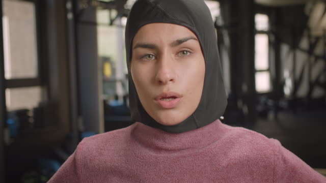 Closeup portrait of young attractive athletic muslim female looking at camera with determination standing in gym indoors