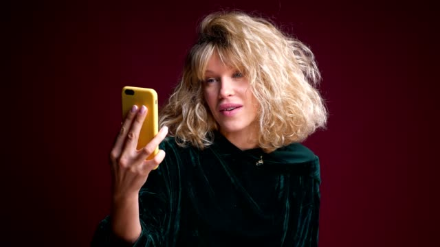 Closeup portrait of young attractive caucasian female having a video call on the phone and making an air kiss in front of the camera