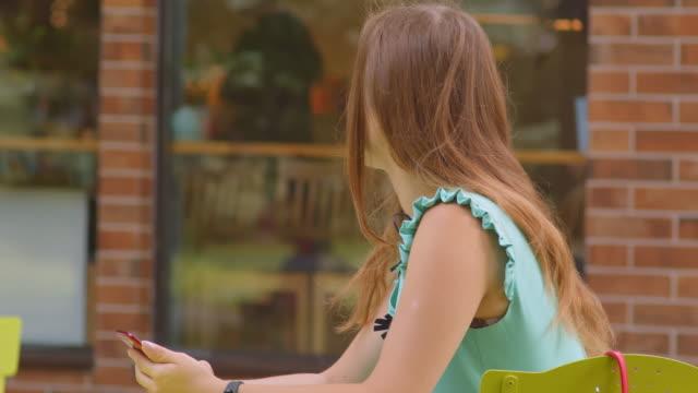 nahaufnahme porträt von jungen attraktiven kaukasischen frau mit telefon sitzen im café im freien - turngerät mit holm stock-videos und b-roll-filmmaterial