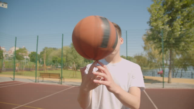 Closeup portrait of young attractive caucasian male basketball player throwing a ball in hoop on the court outdoors with bridge on the background
