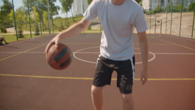 ritratto ravvicinato di giovane attraente giocatore di basket maschile caucasico che lancia una palla nel cerchio sul campo con case sullo sfondo - braccio umano video stock e b–roll