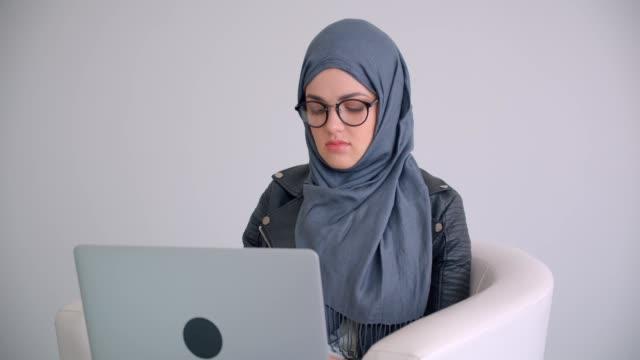 ritratto ravvicinato di giovane attraente imprenditrice musulmana in hijab e occhiali usando il laptop seduto su una poltrona al chiuso in ufficio - libia video stock e b–roll