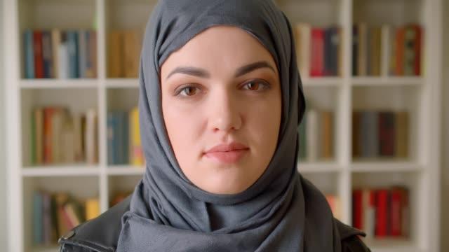 ritratto ravvicinato di giovane studentessa musulmana attraente in hijab che guarda la macchina fotografica nella biblioteca del college al chiuso - libia video stock e b–roll