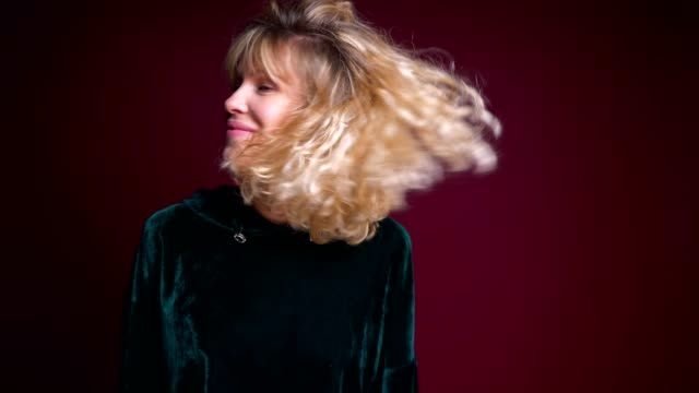 Closeup portrait of young beautiful caucasian female tossing her blond hair and dancing cheerfully in front of the camera.