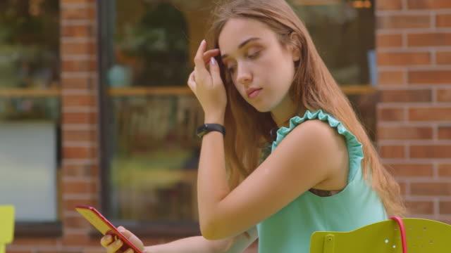 nahaufnahme porträt von jungen schönen kaukasischen frau mit telefon sitzen im café im freien - turngerät mit holm stock-videos und b-roll-filmmaterial