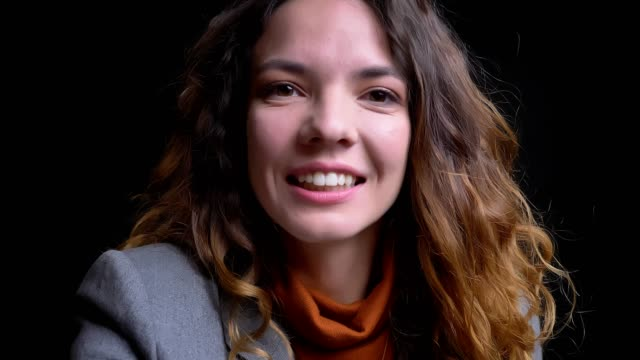 Closeup portrait of young brunette female having a video call on the phone looking at camera waving with a hand and smiling
