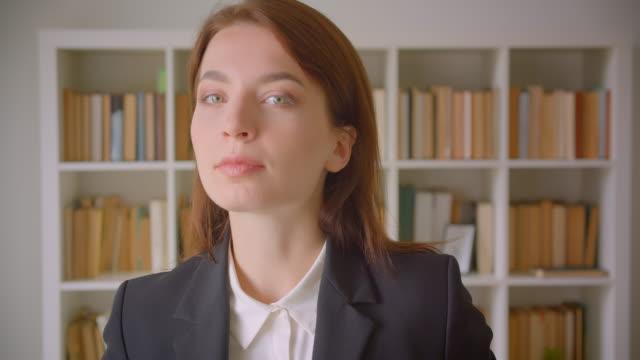 nahaufnahme porträt der jungen kaukasischen geschäftsfrau, die in der bibliothek drinnen fröhlich in die kamera schaut - kosmetik beratung stock-videos und b-roll-filmmaterial