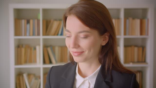 nahaufnahme porträt der jungen kaukasischen geschäftsfrau, die lächelnd in der bibliothek drinnen in die kamera schaut - kosmetik beratung stock-videos und b-roll-filmmaterial