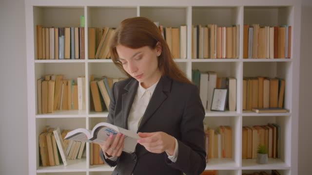 nahaufnahme porträt der jungen kaukasischen geschäftsfrau beim lesen eines buches mit blick auf die kamera in der bibliothek - kosmetik beratung stock-videos und b-roll-filmmaterial