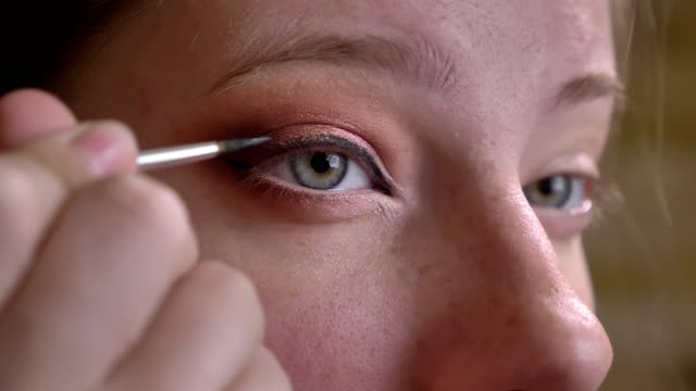 Closeup portrait of young caucasian female makeup artist applying black eyeliner for stunning arrows Closeup portrait of young caucasian female makeup artist applying black eyeliner for stunning arrows. eyeliner stock videos & royalty-free footage