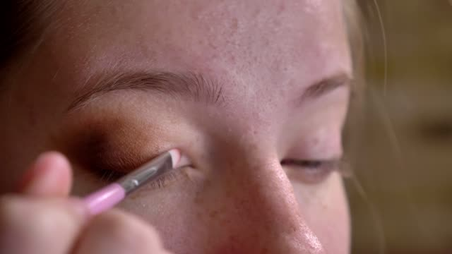 Closeup portrait of young caucasian female makeup artist applying brown eyeshadow to her upper eyelid Closeup portrait of young caucasian female makeup artist applying brown eyeshadow to her upper eyelid. eyeliner stock videos & royalty-free footage