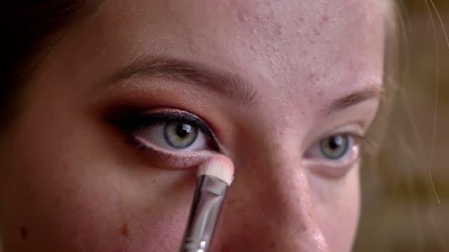 vídeos de stock e filmes b-roll de closeup portrait of young caucasian female makeup artist applying white eyeshadows to the eye corner - sombra para os olhos