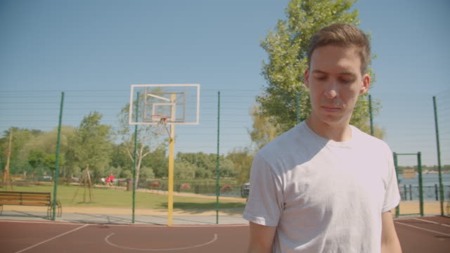 Closeup portrait of young caucasian male basketball player spinning a ball on the finger on the court outdoors with bridge on the background