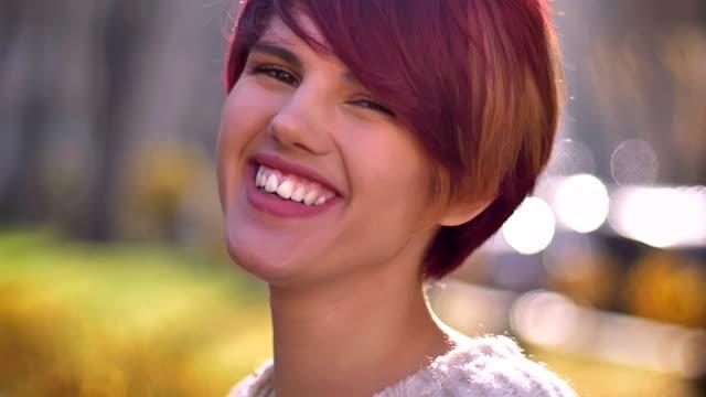 stockvideo's en b-roll-footage met close-up portret van jonge kaukasische roze harige meisje draaien om de camera en bescheiden lachen op de herfst park achtergrond. - roze haar