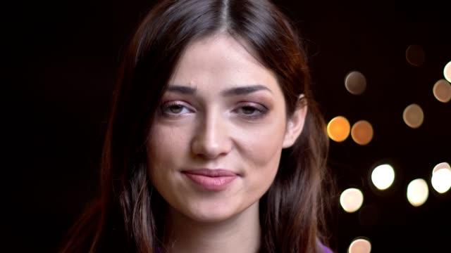 stockvideo's en b-roll-footage met close-up portret van jonge schattige kaukasische vrouwelijke glimlachend vrolijk en kijken recht op camera met nachtlampje op de achtergrond - portrait background