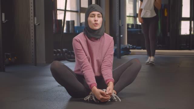 närbild porträtt av unga bestäms atletisk muslim hona i hijab stretching ben i gymmet inomhus - anständig klädsel bildbanksvideor och videomaterial från bakom kulisserna