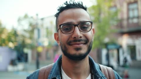 ritratto ravvicinato di giovane bel arabo in piedi all'aperto da solo sorridente - people video stock e b–roll