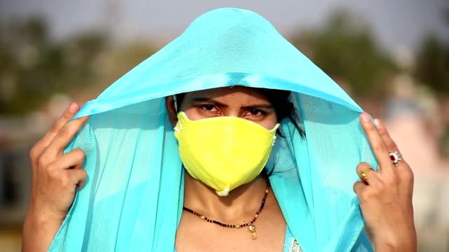 Retrato de perto de jovens mulheres tradicionais indianas cobrindo o rosto com máscara de poluição durante a Pandemia de Coronavirus, Índia - vídeo