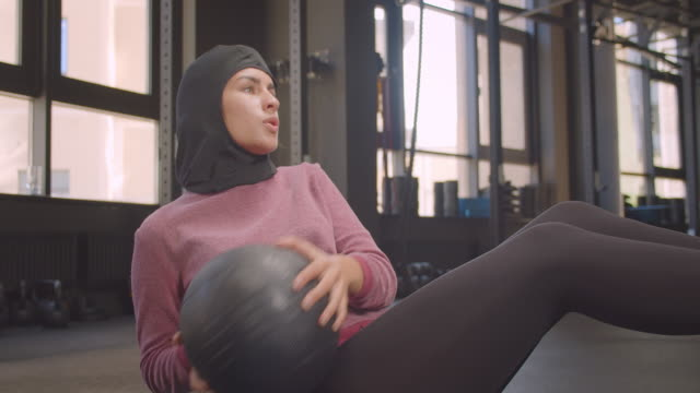 Closeup portrait of young motivated athletic muslim female in hijab working out with ball in gym indoors