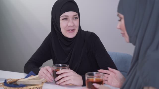 close-up portrait of young muslim woman in black hijab smiling and talking with friend. two women communicating indoors and drinking hot tea. friendship, lifestyle. - abbigliamento modesto video stock e b–roll