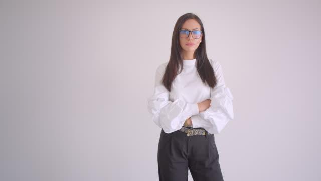 nahaufnahme porträt der jungen hübschen kaukasischen geschäftsfrau in brille mit armen über brust gekreuzt blick auf die kamera mit hintergrund isoliert auf weiß - kosmetik beratung stock-videos und b-roll-filmmaterial
