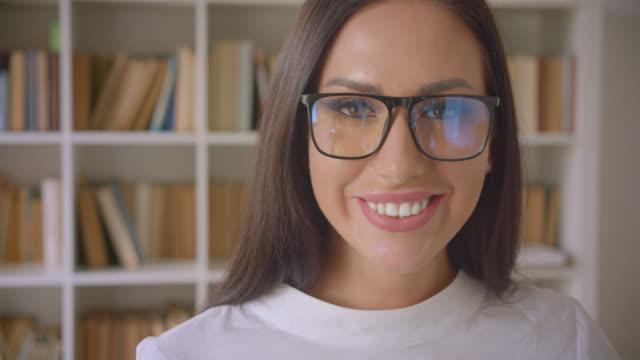 nahaufnahme porträt der jungen hübschen kaukasischen geschäftsfrau in brille, die auf die kamera schaut und glücklich drinnen mit bücherregalen im hintergrund lächelt - kosmetik beratung stock-videos und b-roll-filmmaterial