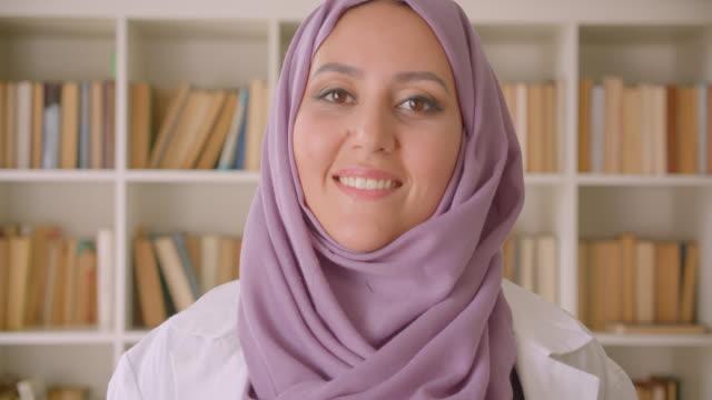 ritratto ravvicinato della giovane dottoressa musulmana in hijab che guarda la telecamera sorridere felicemente in biblioteca - cultura del medio oriente video stock e b–roll