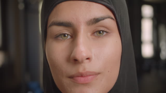 Closeup portrait of young successful athletic muslim female looking at camera with determination standing in gym indoors