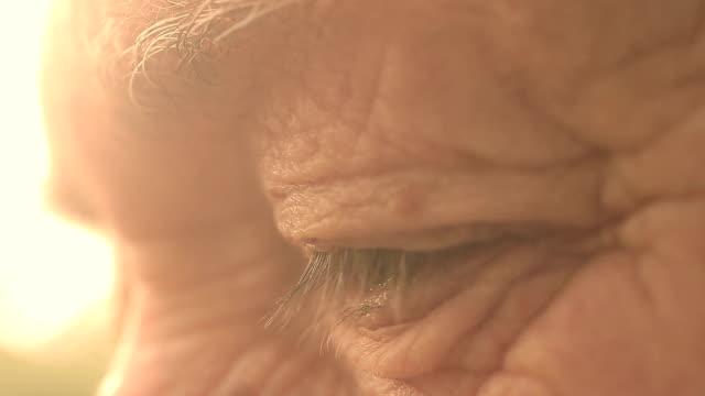 portrait de gros plan sur les yeux d'un homme âgé avec rétro-éclairage du soleil: Regardez, wrinled homme - Vidéo
