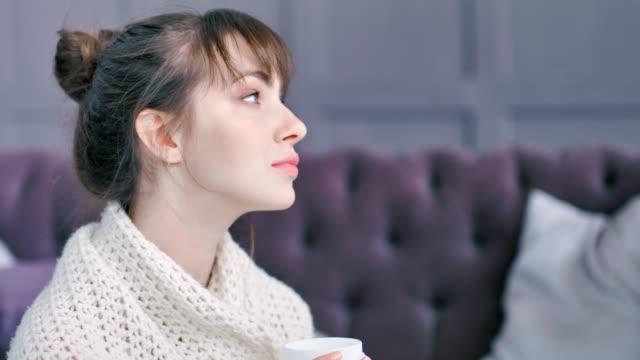 closeup portrait romantische inländischen junge frau trinken halten tasse heißgetränk in plaid gewickelt - cozy stock-videos und b-roll-filmmaterial