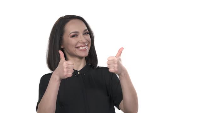 närbild porträtt skott av en leende kvinna som visar tummen upp. kroppsspråk och gester. isolerad, vit bakgrund - thumbs up bildbanksvideor och videomaterial från bakom kulisserna
