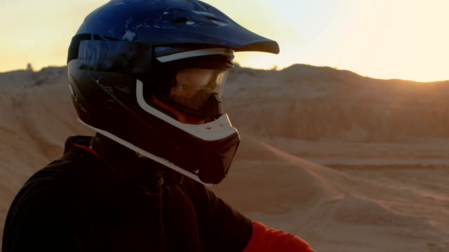 close-up portrait shot of the extreme motocross rider in a cool protective helmet standing on the off-road terrain he's about to overcome. background is sandy track. - motocross video stock e b–roll