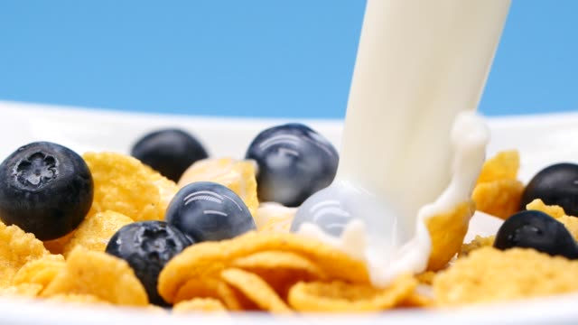 Close-up pouring milk into a bowl with cereals and blue berries, slow motion video